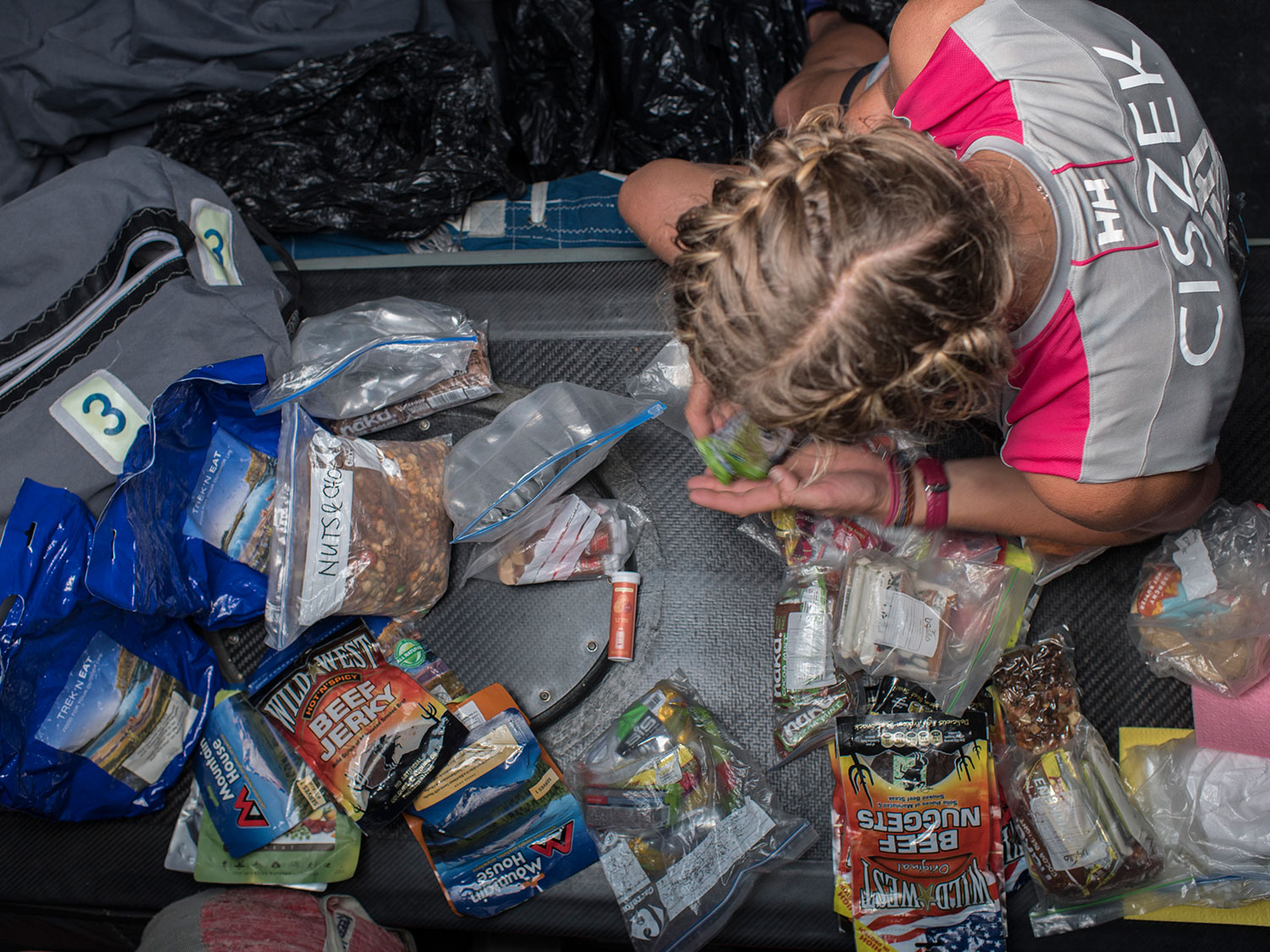 Sophie Ciszek organizes and consolidates a few food bags. The boat carries only freeze dried foods
