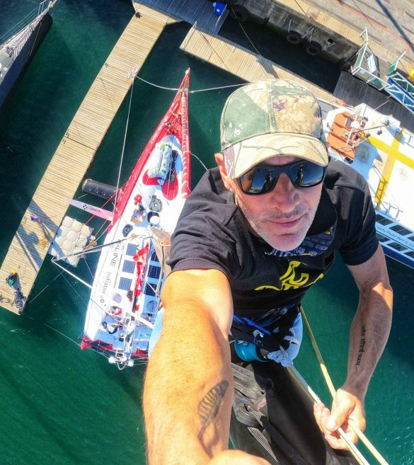 Jeff Ayliffe climbs the mast of Sam Davies' Imoca 60 in Cape Town